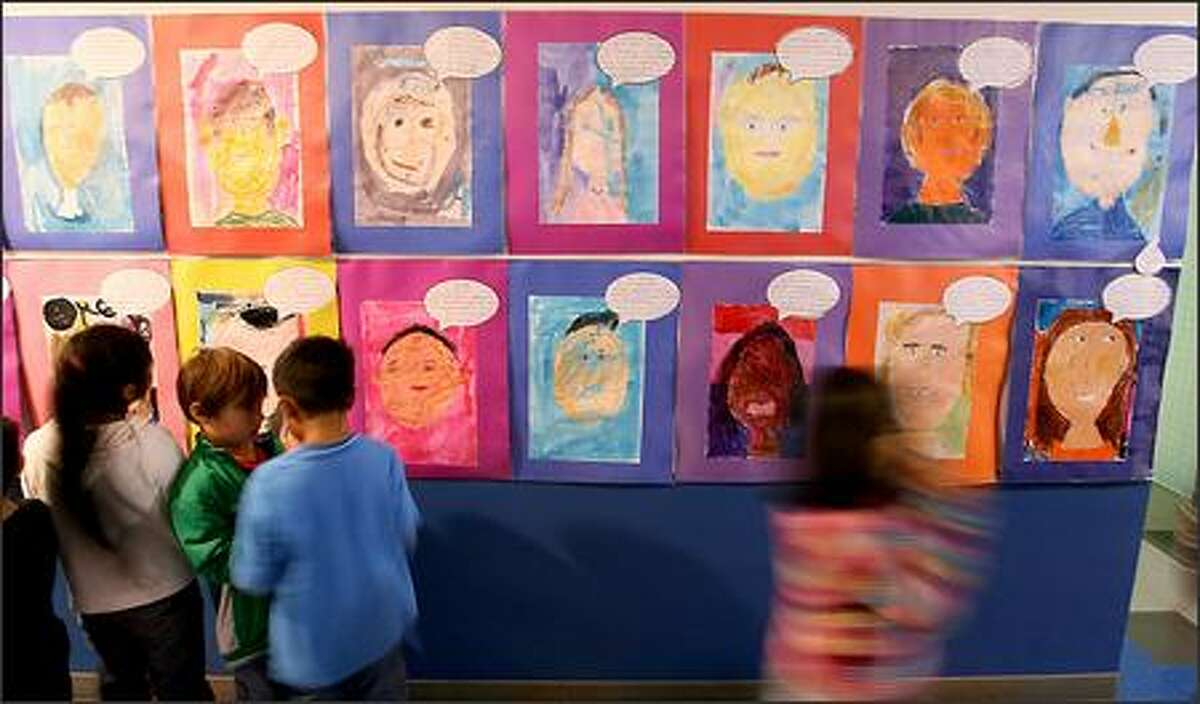 Second-graders in Tom DeFelice's class view the artwork that lines the hallways at Adams Elementary School.