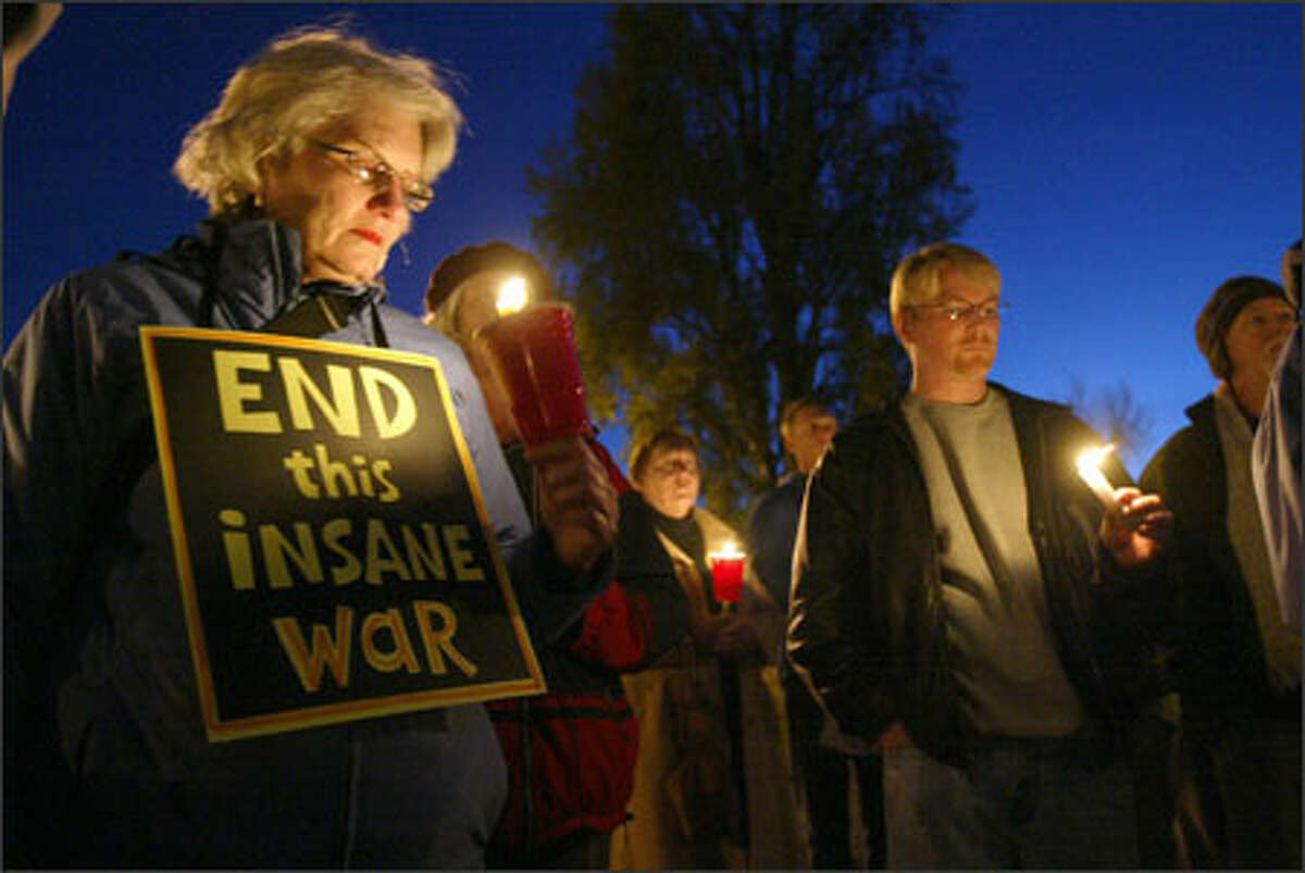 Cheryl Banks of West Seattle gathers with about 100 people at Alki Beach Wednesday night to mourn the 2,000 U.S. military personnel who have been killed in Iraq.