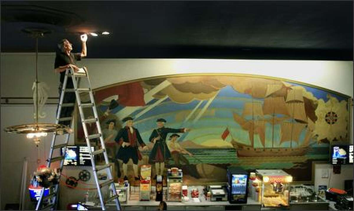 An early-1940's mural provides the backdrop to the concession stand as promotional manager Steve Garrett replaces ceiling lights in the lobby of the Admiral Theater in West Seattle.