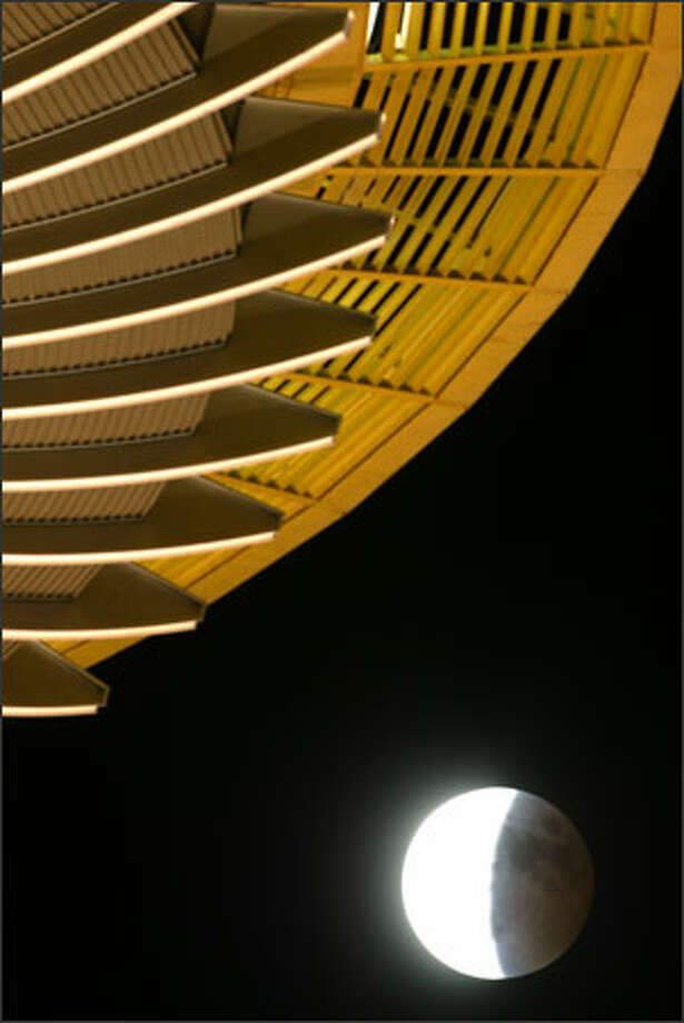 The moon emerges from the earth's shadow as it moves southeast through the Seattle sky during Wednesday's lunar eclipse, as viewed from beneath the Space Needle. Photo: Karen Ducey, Seattle Post-Intelligencer / Seattle Post-Intelligencer