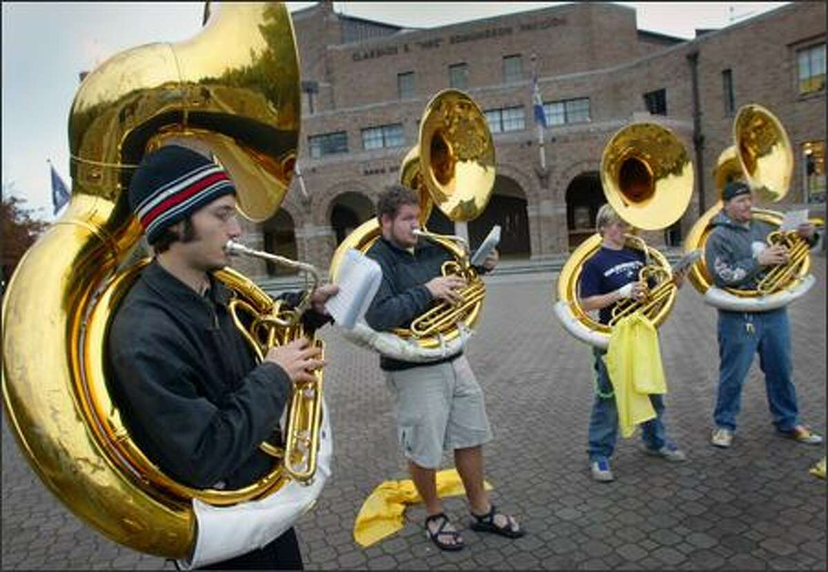 Members of the University of Washington marching band's brass section -- sousaphonists, from left, Peter Daniell, Ian Buchanan, Val Scrivner and Chris Buol -- practice yesterday in front of Hec Edmundson Pavilion. The marching band is a 240-member ensemble that adds energy to UW sporting events. The band is celebrating its 75th anniversary this school year.