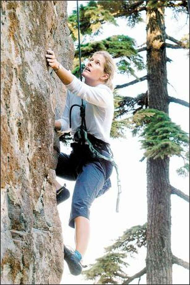 Terri Sanders of Bellevue makes her move on the Peanut Brittle route on Peannacle Wall in the Deception Crags area off Exit 38. Photo: Meryl Schenker, Seattle Post-Intelligencer / Seattle Post-Intelligencer