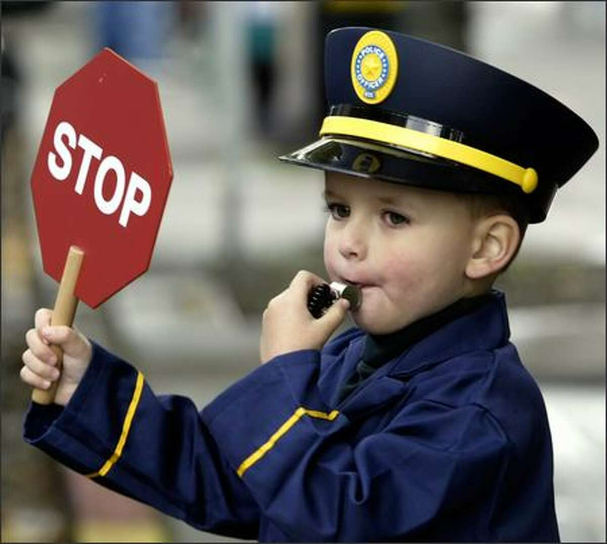 Ben Davis, 3 1/2, of Mercer Island plays the role of the traffic cop he's dressed as, holding up a stop sign and blowing his whistle at a pedestrian crosswalk on Alaskan Way on Sunday during Trick or Treat on the Waterfront, sponsored by the Seattle Aquarium.