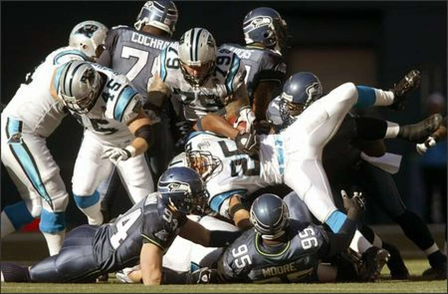 Seattle Seahawks defense turns Carolina Panthers Joey Harris on sideways in the first quarter. Photo: Mike Urban, Seattle Post-Intelligencer / Seattle Post-Intelligencer