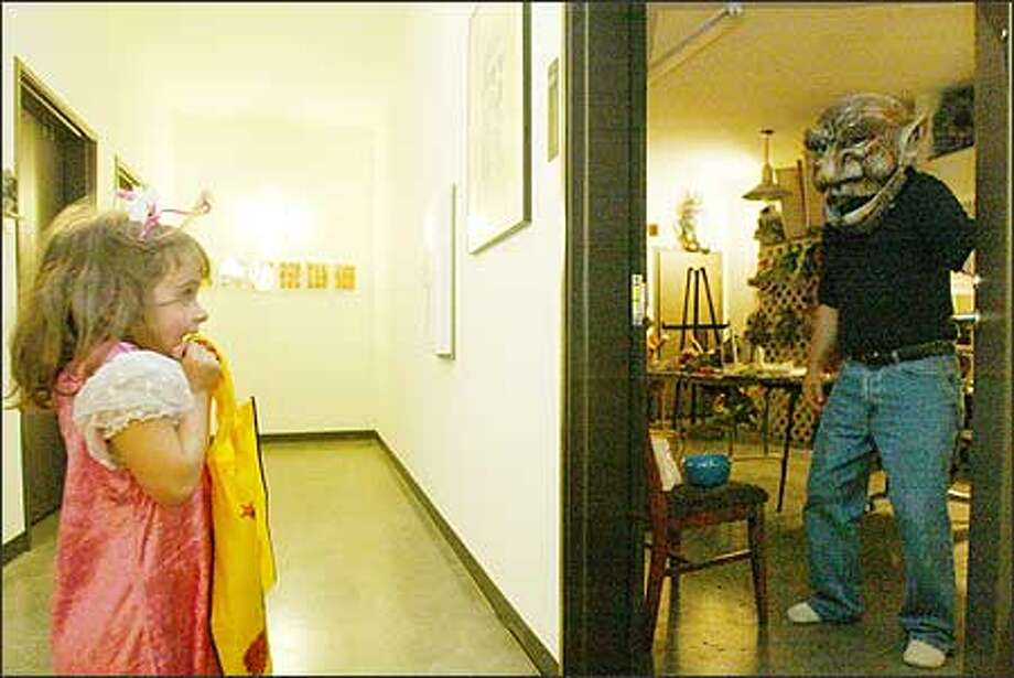 Gretta Woodall, 5, gets quite a start as artist Roger Wheeler greets her in a troll mask he made at the Tashiro Kaplan Artist Lofts on Halloween. Gretta lives there with her parents, George Woodall and Marina Shubina Woodall. Photo: Gilbert W. Arias, Seattle Post-Intelligencer / Seattle Post-Intelligencer