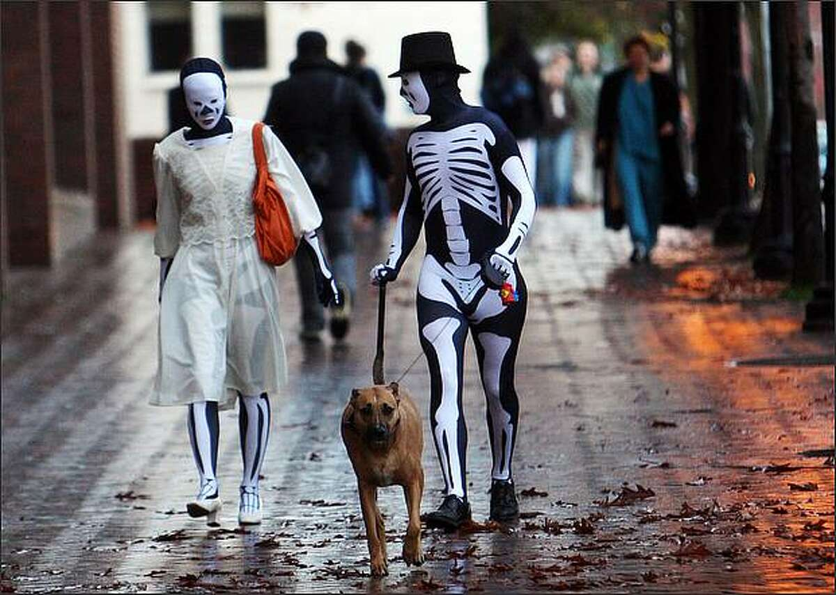 A pair of skeletons walk a dog on Broadway on Capitol Hill in Seattle on Halloween.