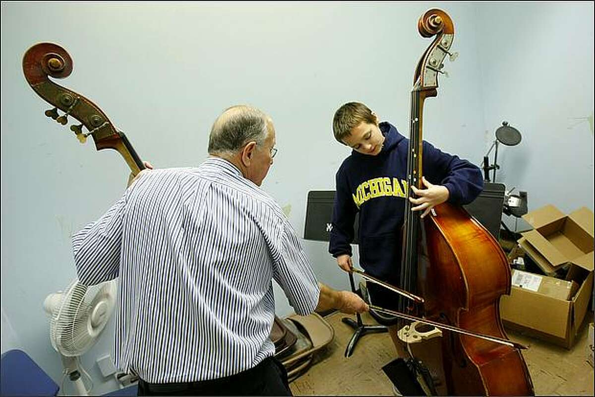 Angelo Lucia, 12, receives instruction on the bass viol from Fred Strom, who is among a number of musicians with the Seattle Philharmonic Orchestra who volunteer as tutors to students learning stringed instruments at Meany Middle School in Seattle.