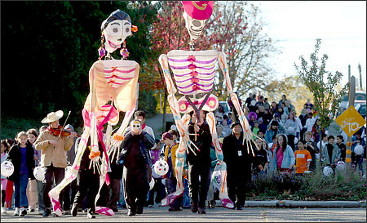 John Stanford International School students carry skeleton puppets during a Dia de los Muertos, or Day of the Dead, parade in Wallingford Friday, Oct. 31. Students at the school, as well as those at Hamilton International Middle School, have been working with artists Fulgencia Lazo and Nathan Scott as they learn about Day of the Dead traditions in remembrance of deceased loved ones.