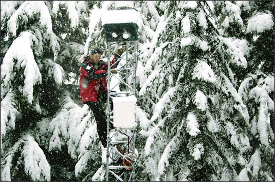Chet Mowbray, snow safety director at Crystal Mountain, climbs down a weather-station tower after checking on the device that measures precipitation. Photo: Dan DeLong, Seattle Post-Intelligencer / Seattle Post-Intelligencer