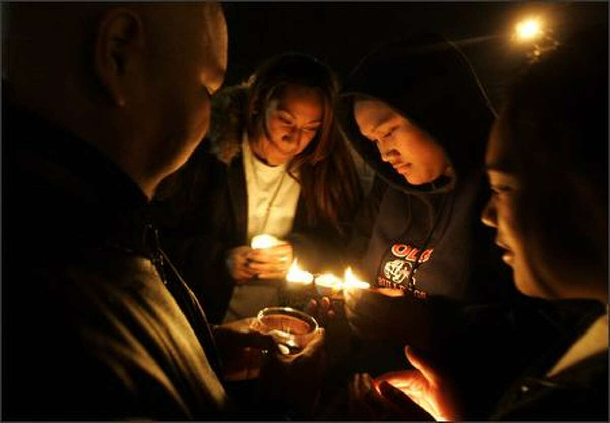 Ken Taitai, left, Temalisa Moimoi, Katalina Aho and Salote Moimoi participate in a candlelight protest of school closures Wednesday at the John Stanford Building.