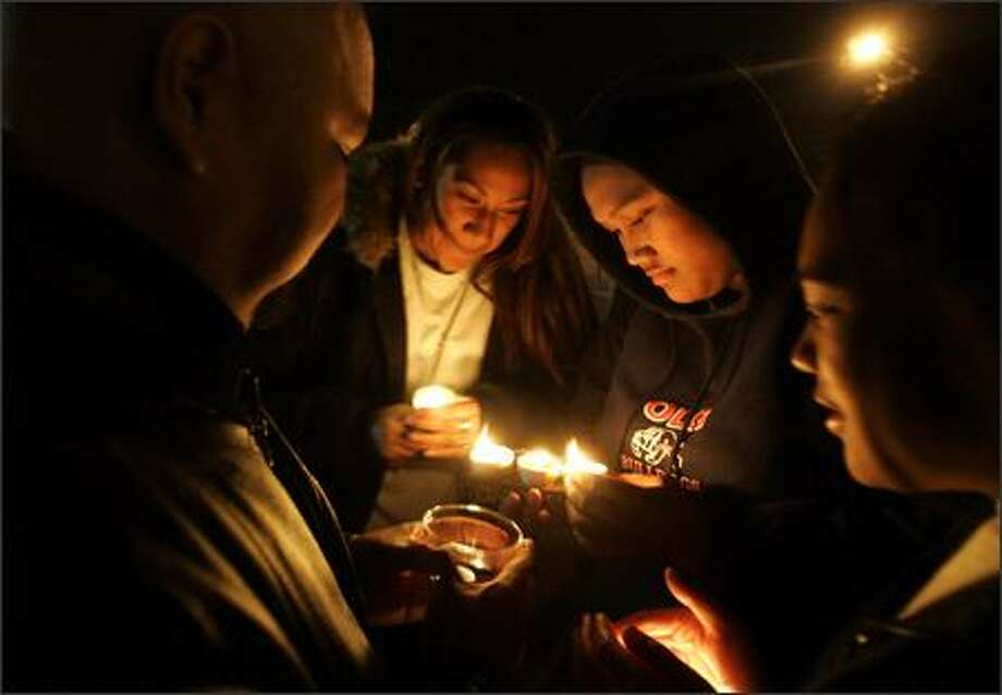 Ken Taitai, left, Temalisa Moimoi, Katalina Aho and Salote Moimoi participate in a candlelight protest of school closures Wednesday at the John Stanford Building. Photo: Mike Kane, Seattle Post-Intelligencer / Seattle Post-Intelligencer