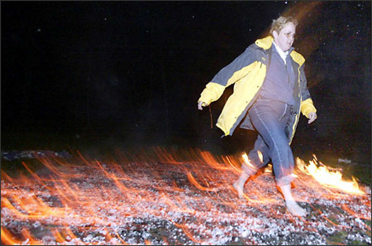 Share DeWees, of Gig Harbor, walks across a bed of coals estimated at 1,200 degrees Fahrenheit. She was participating in a firewalking event on Saturday, Nov. 1, at the UKO Karate School in Port Orchard.