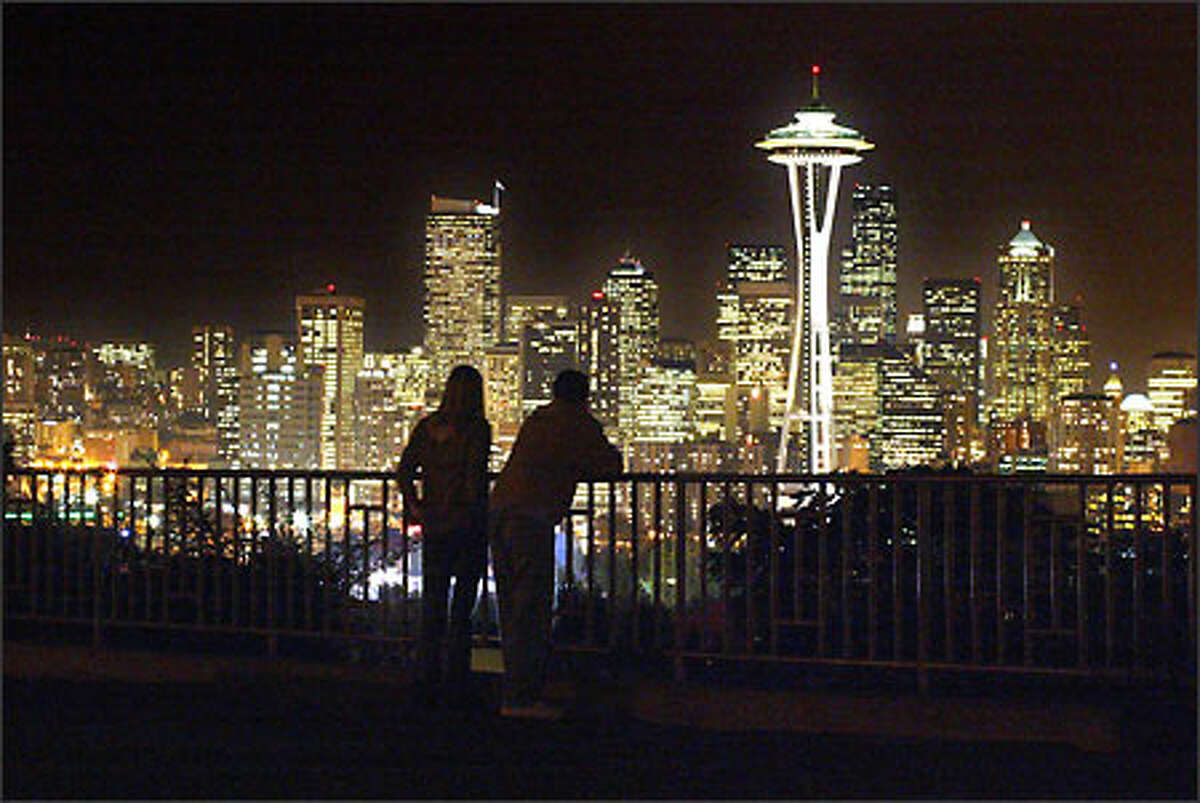 A couple stop just after sunset to take in the view of Seattle's skyline recently from Kerry Park on Queen Anne Hill.