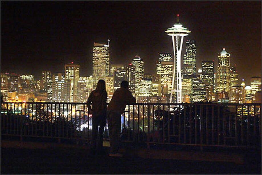 A couple stop just after sunset to take in the view of Seattle's skyline recently from Kerry Park on Queen Anne Hill. Photo: Gilbert W. Arias, Seattle Post-Intelligencer / Seattle Post-Intelligencer