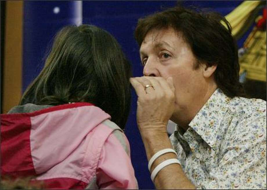 Paul McCartney whispers the ending of his new children's book in the ear of Jade Lauw, a second-grader at Briarcrest Elementary School in Shoreline, during a reading Friday at Third Place Books in Lake Forest Park. Also in attendance was one very excited P-I reporter ... Photo: Dan DeLong, Seattle Post-Intelligencer / Seattle Post-Intelligencer