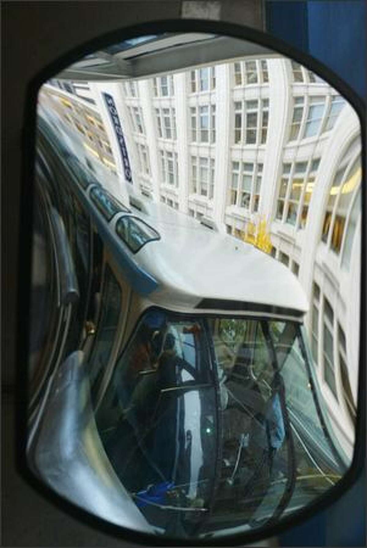 A mirror reflection shows the Seattle Monorail's blue train pulls into Westlake Center. The popular tourist attraction is back in service after months of tests and maintenance following two stalls during the summer.