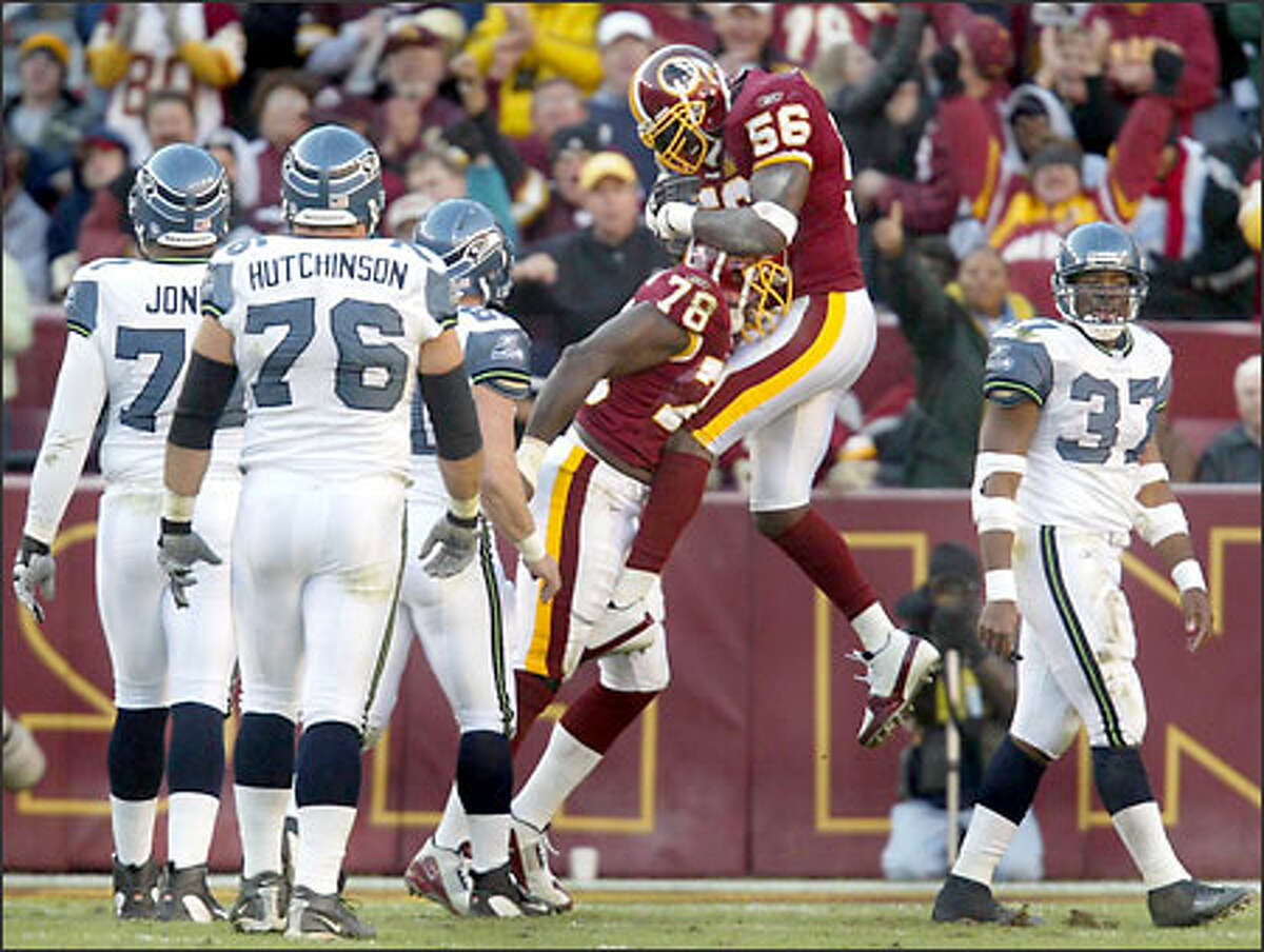 Seahawks players look on as Redskins defensive lineman Bruce Smith (78) gets mugged by teammate LaVar Arrington (56) following a third-quarter sack of Seahawks quarterback Matt Hasselbeck to put him a half sack behind all-time sacks leader Reggie White.