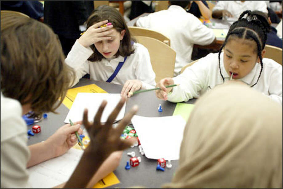 "Meany Middle School ""mathletes"" Shannon Ryan, center, and LaDonna Wilson, right, work with teammates on algebra problems during an ""Algebrathon"" at Madrona K-8 in Seattle. The event is part of an extended-day program at Madrona and Meany Middle School, where sixth- and seventh-graders stay after school two days a week to learn math. The ""Assist With Algebra"" program was created by the schools with help from Seattle Sonic Ray Allen's Ray of Hope Foundation and Gear-Up. The students were awarded prizes and dinner. Photo: Joshua Trujillo, Seattlepi.com / Seattle Post-Intelligencer"