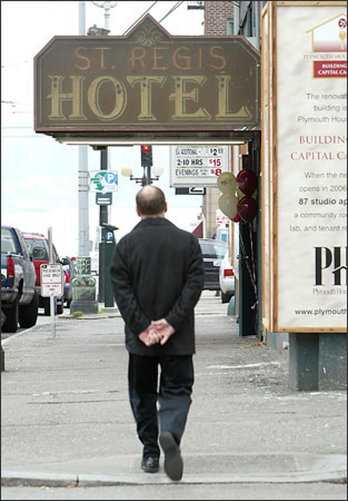 A pedestrian strolls past the old St. Regis Hotel at Second and Stewart in downtown Seattle.