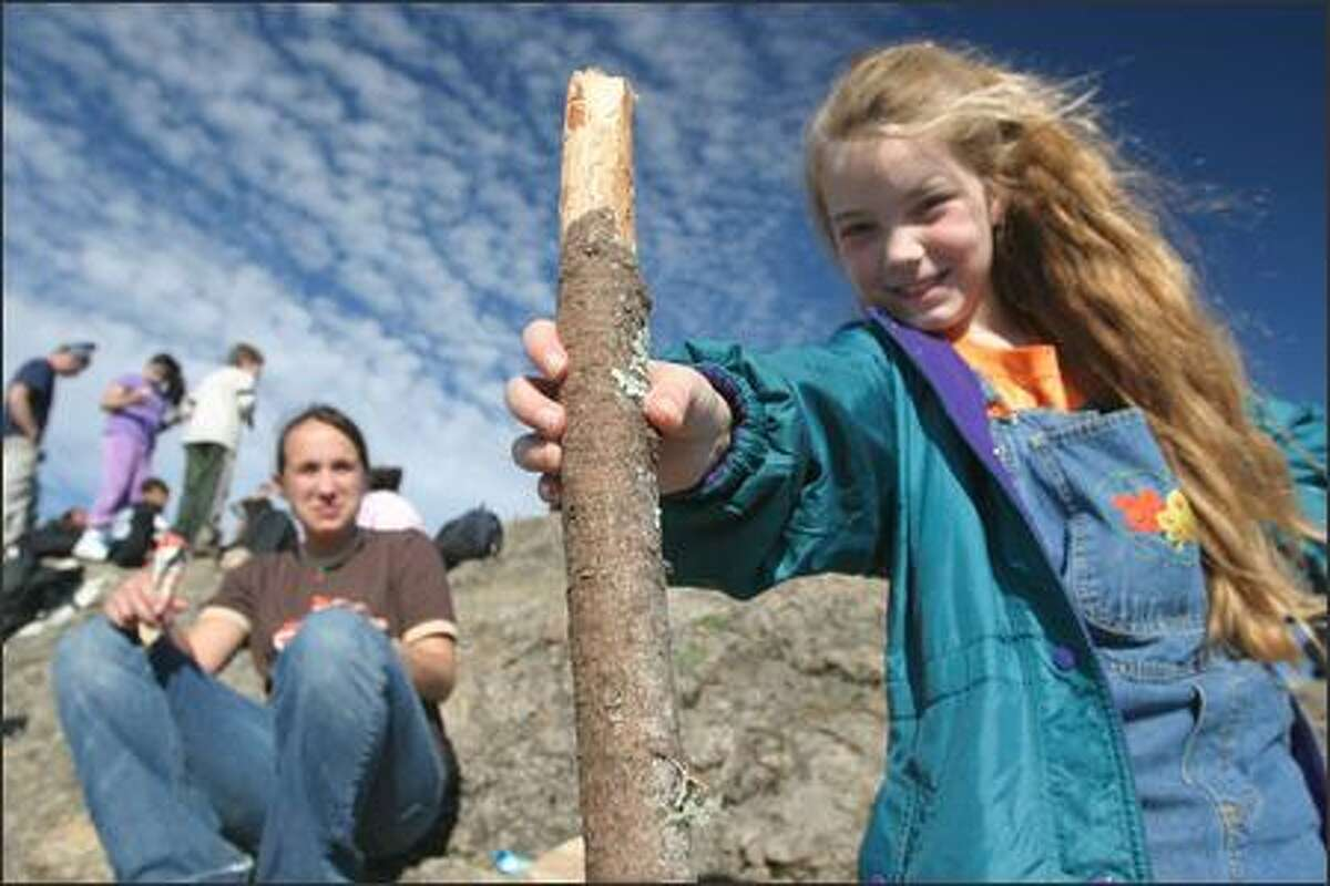 Tukwila Elementary student Karri Bures, 8, shows off her walking stick on top of Rattlesnake Ledge after a two-mile hike with Inner City Outings.