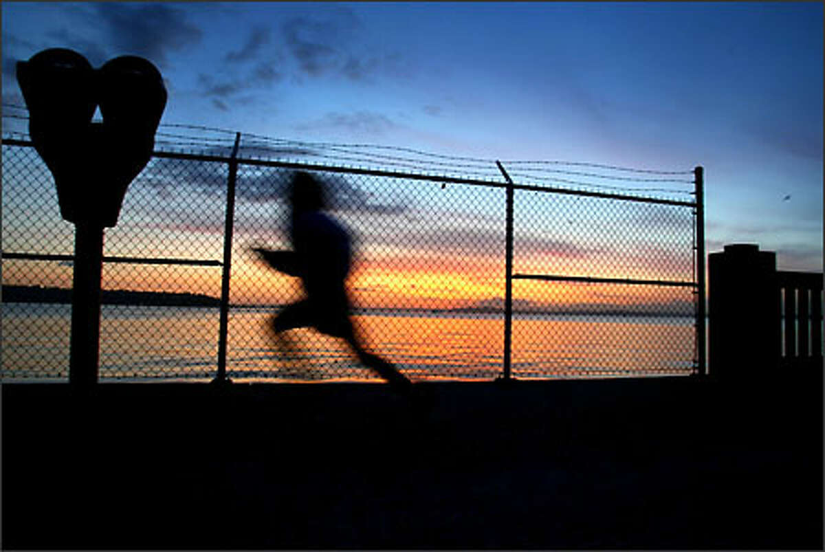 A child runs through the parking lot in Myrtle Edwards Park as the sun sets.