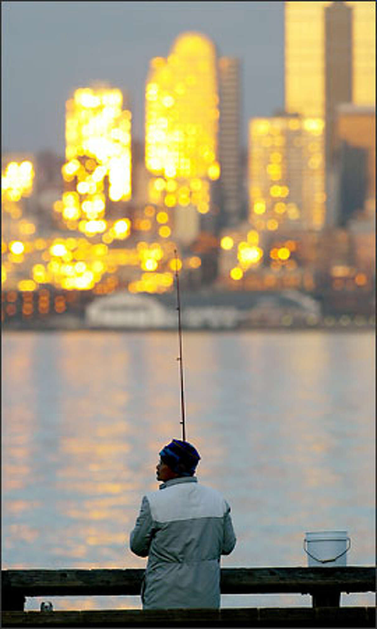 Chi Ti enjoys the sunset reflected off buildings in downtown Seattle as he jigs for squid at Seacrest Marina in West Seattle Tuesday evening.
