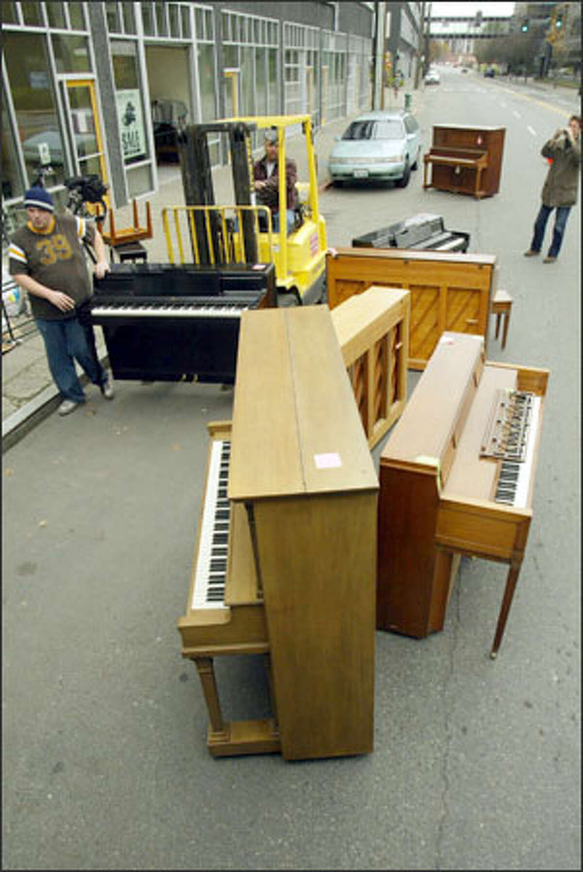 Mike Ballou from Pro Piano Move, left, transports one of 36 in Seattle for later shipment to Kenya. Seattle Piano Gallery sends old pianos to a Kenyan-owned repair business, which fixes them and sells them. The gallery says pianos and work are badly needed in Kenya. If anyone wishes to donate an old piano, the gallery will pay for pick up, moving and storage.