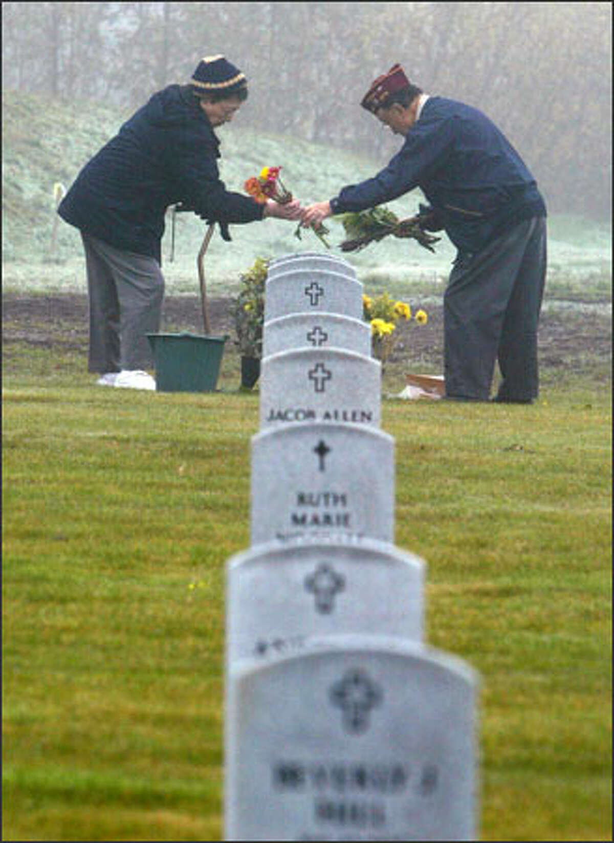 U.S. Army veteran Roy Fujiwara, 87, and his wife, Sci, arrange flowers at the grave of Roy's brother, Yoshio Fujiwara, before the Veterans Day program at Kent's Tahoma National Cemetery. The Japanese American brothers served in World War II. More than 1,000 joined in Veterans Day ceremonies at the cemetery.