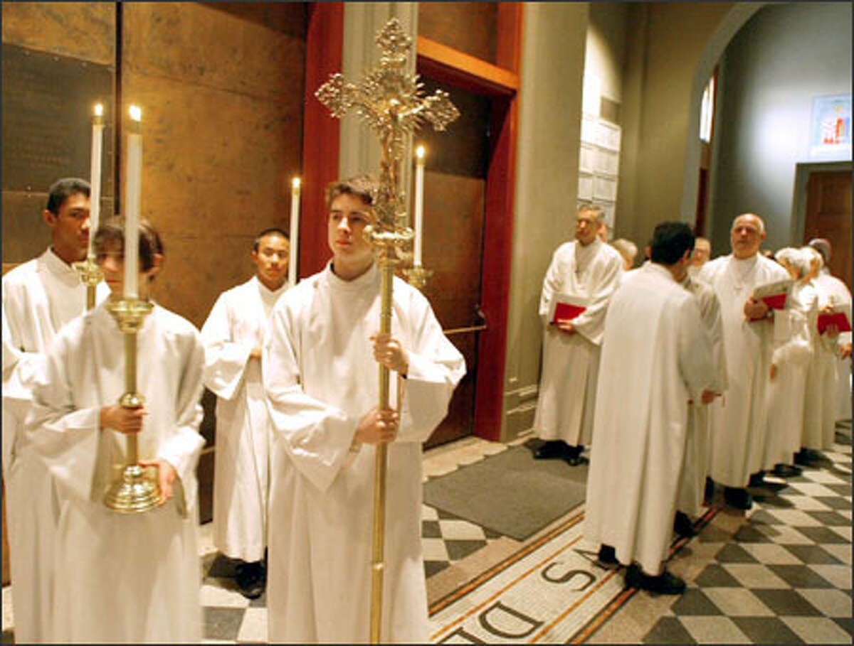 Liturgical ministers, including cross bearer Matt Davis, wait for their processional to begin at a recent service at St. James Cathedral in Seattle.
