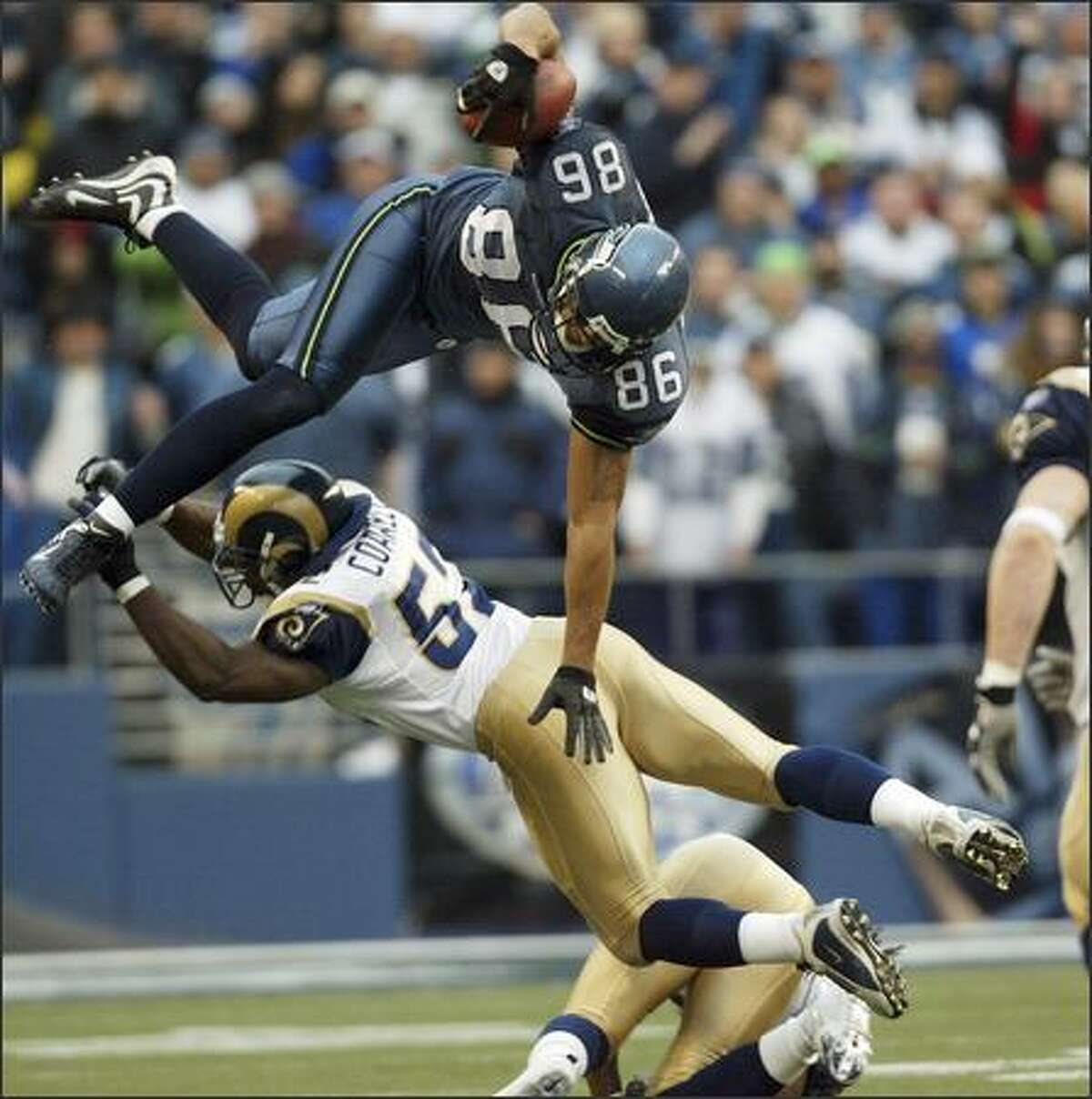 Seattle Seahawks' Jerramy Stevens leaps over St. Louis Rams Dexter Coakley during the second quarter of last Sunday's game at Qwest Field. Seattle won 31-16.