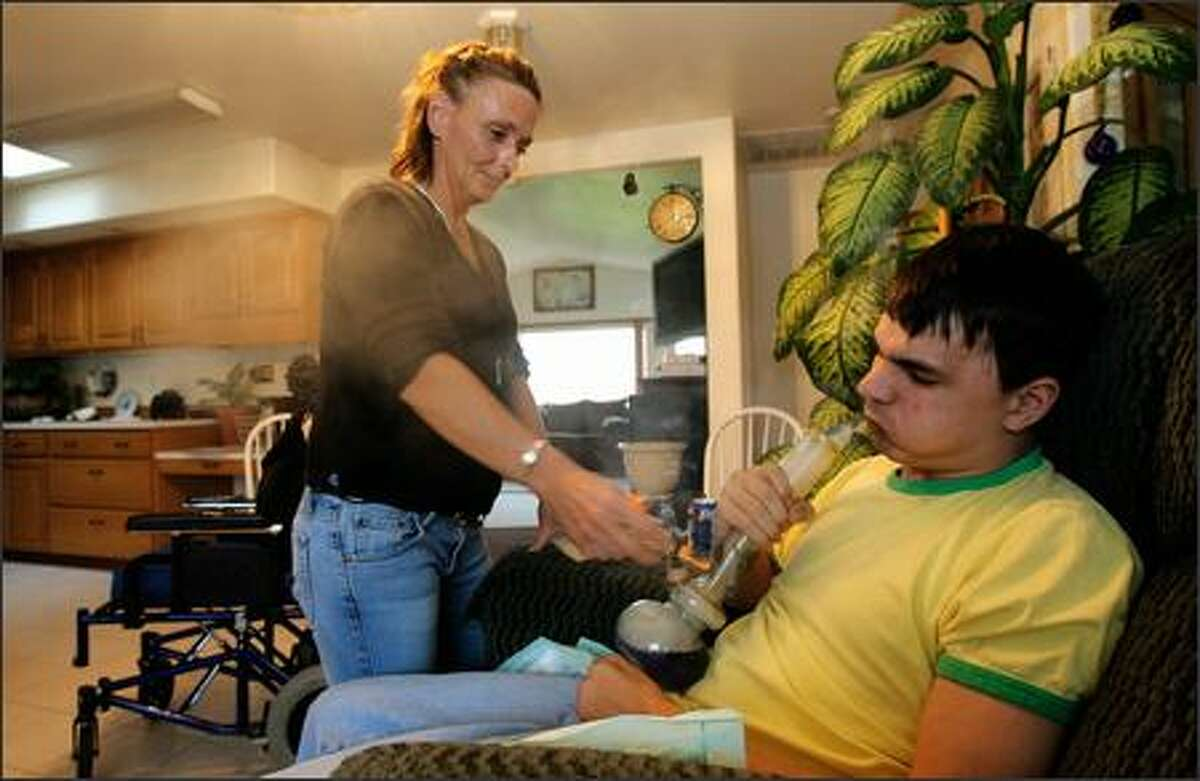 Robin DeBow helps son Chris Chastain light his bong filled with marijuana at their home in Winlock. Chastain was severely injured in a car accident and was authorized to use marijuana for medical reasons. His mother was growing it at home for him -- until she got busted.