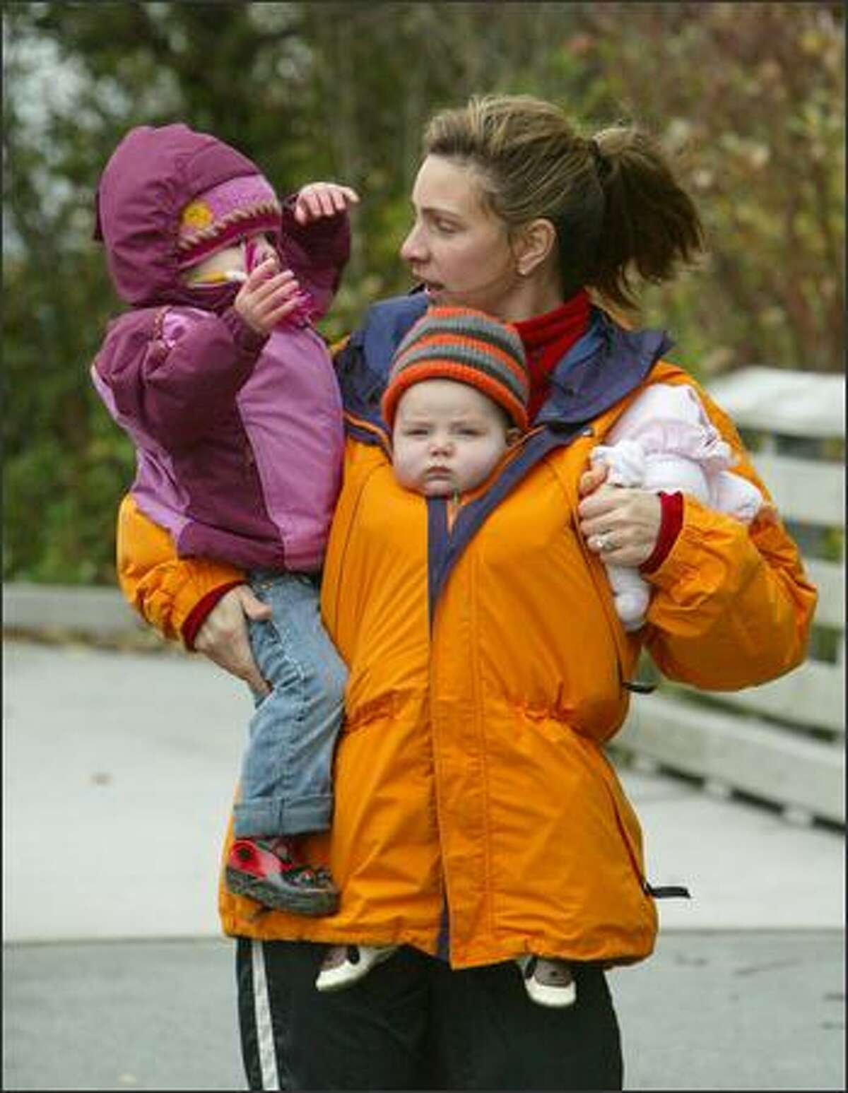 Jennie Bowen stops to talk with Frankie, 2, as Noah, 4 months, hangs in after a walk along the beach at Golden Gardens Park in Seattle on a blustery Monday.