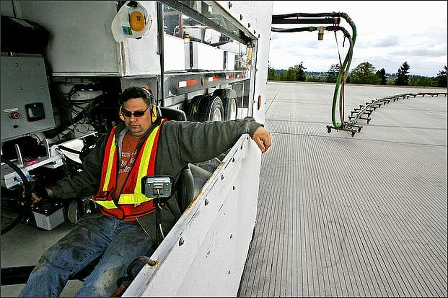 Cardinal Grooving Co. employee Mark Beck cuts small grooves to help disperse rainwater from the third runway at SeaTac airport. Photo: Gilbert W. Arias, Seattle Post-Intelligencer / Seattle Post-Intelligencer