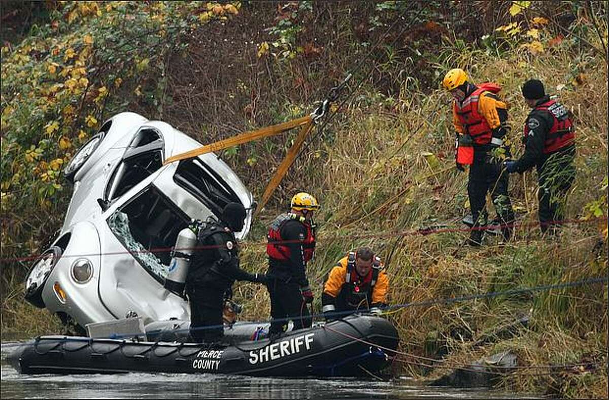 Divers removed a car submerged in the Green River, but found only the body of a 2-year-old boy inside. A 13-year-old boy who was also in the car Friday when it plunged into the river is still missing, and crews from the King County Sheriff's Office searched for his body until nightfall. The 2-year-old was found still strapped into his car seat.