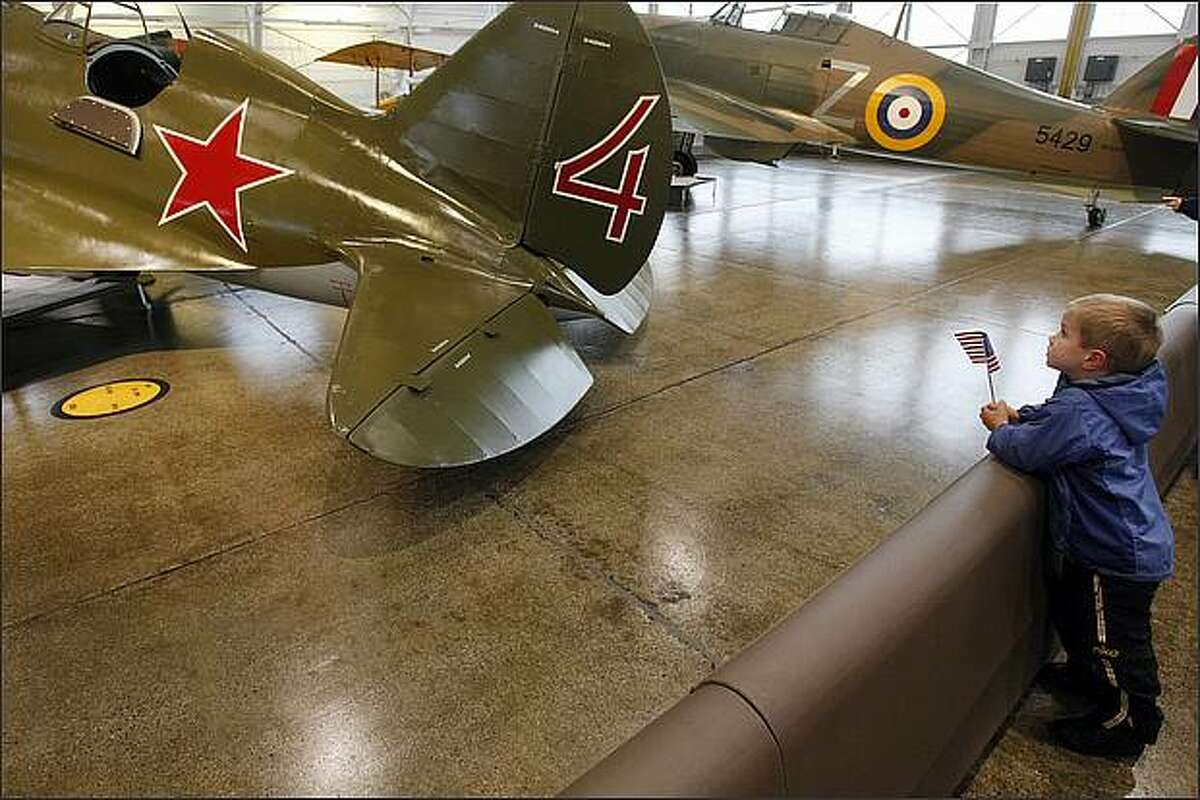 Trevor Plough, 4, of Machias, Wash. looks at vintage, last-of-a-kind planes at the Flying Heritage Collection in Everett before the beginning of their Veterans Day event