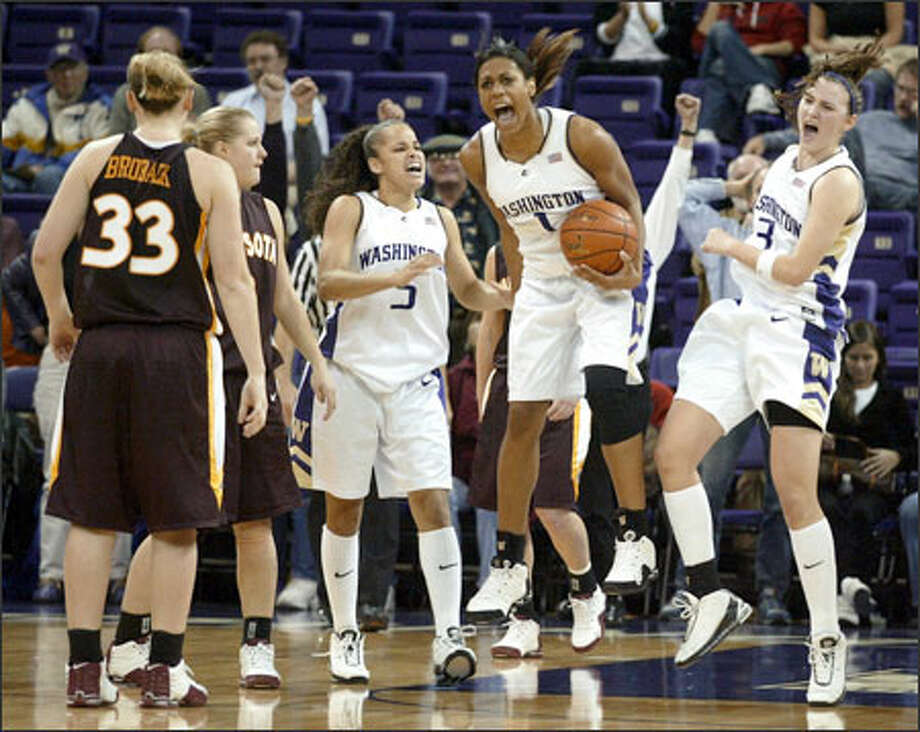 Washington's Jill Bell, center, Cameo Hicks, left, and Breanne Watson, right, celebrate grabbing the final rebound after Minnesota failed to convert a 3-pointer in the last seconds of overtime, giving the Huskies (2-0) a 72-67 win over the No. 14-ranked Gophers in the championship game of the WBCA/BTI Classic at Hec Edmundson Pavilion. Photo: Mike Urban, Seattle Post-Intelligencer / Seattle Post-Intelligencer