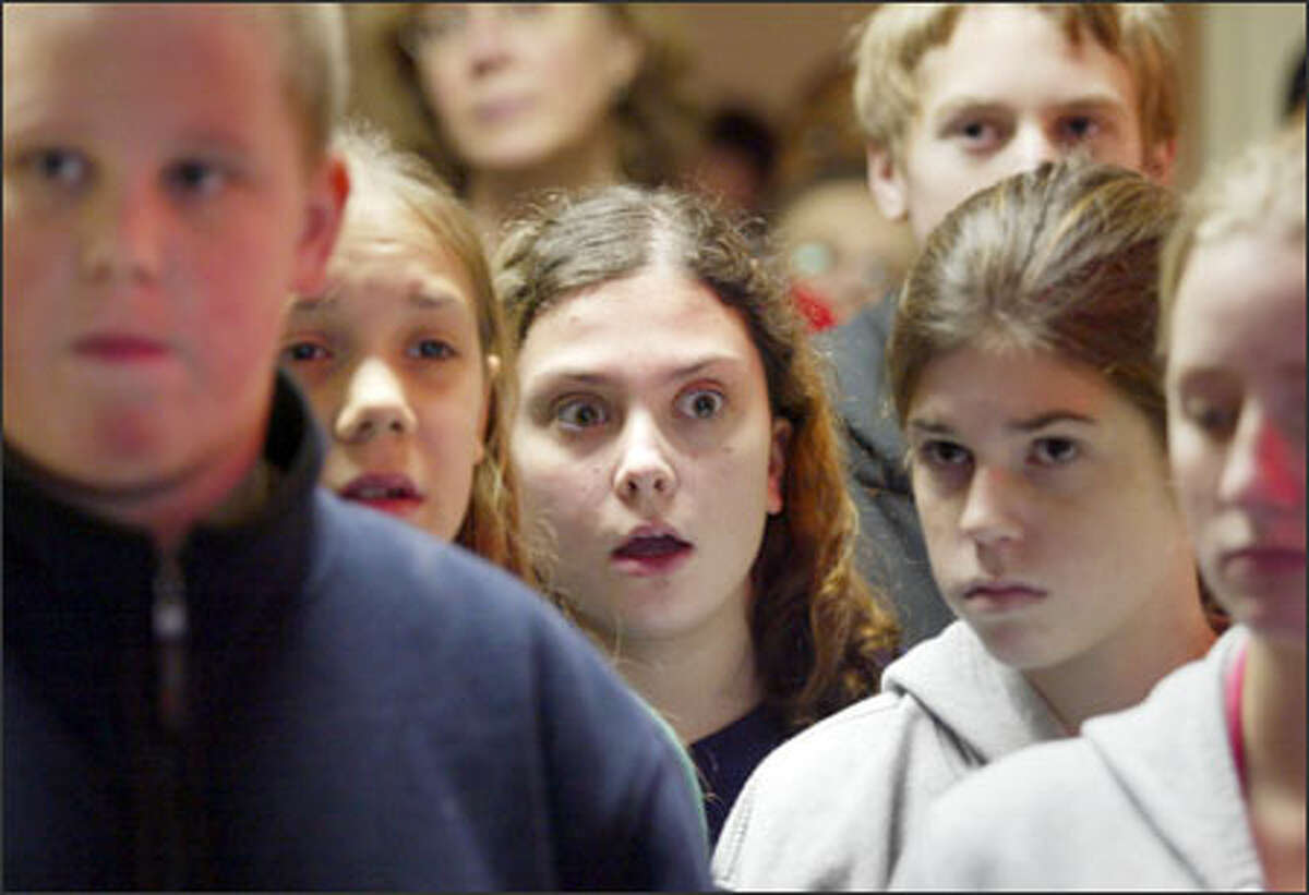 Shoreline Christian School eighth-grader Marie Turner, 13, reacts to a video showing conditions in a children's hospital in Moldova. Other displays at