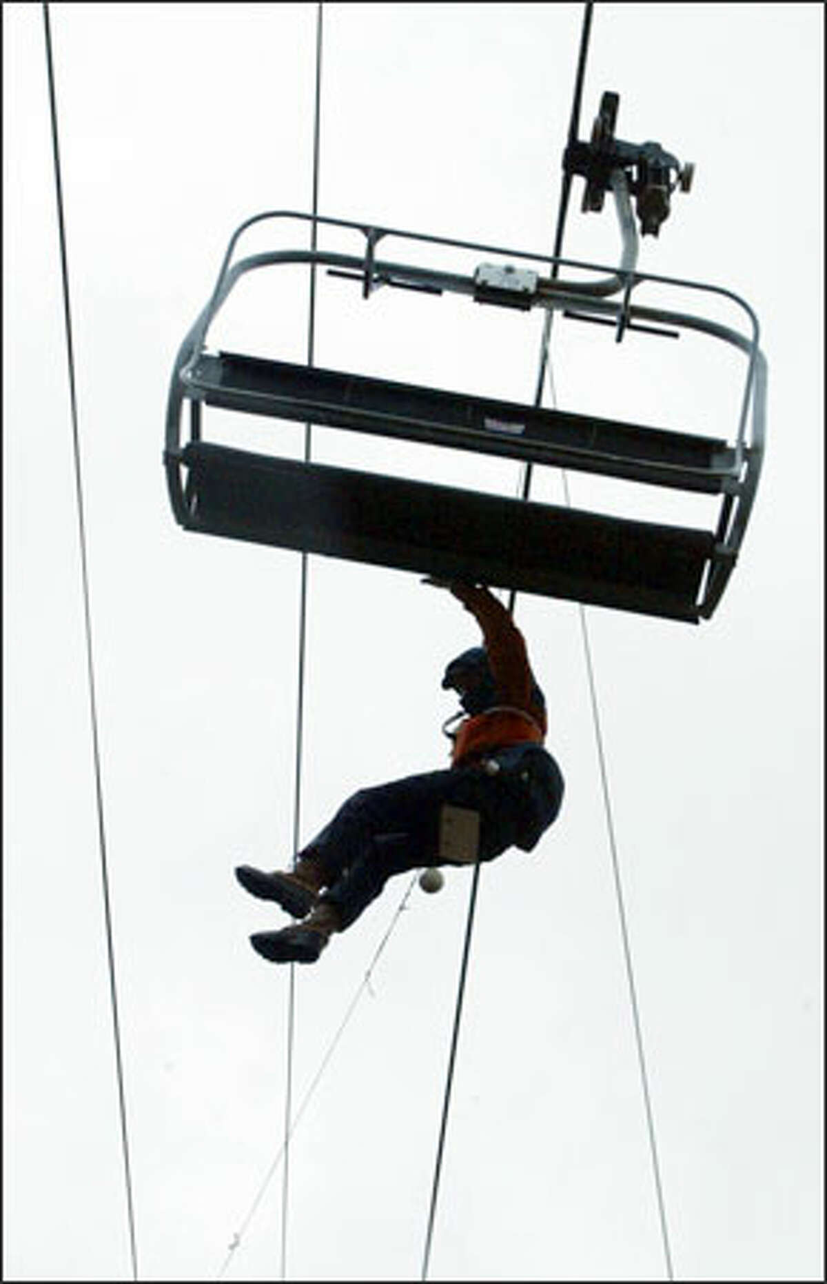 Dave Buck is lowered off the chairlift at Summit Central at Snoqualmie Pass during training exercises for volunteers. The chair evacuation is one of many skills that members of the ski patrol must learn.