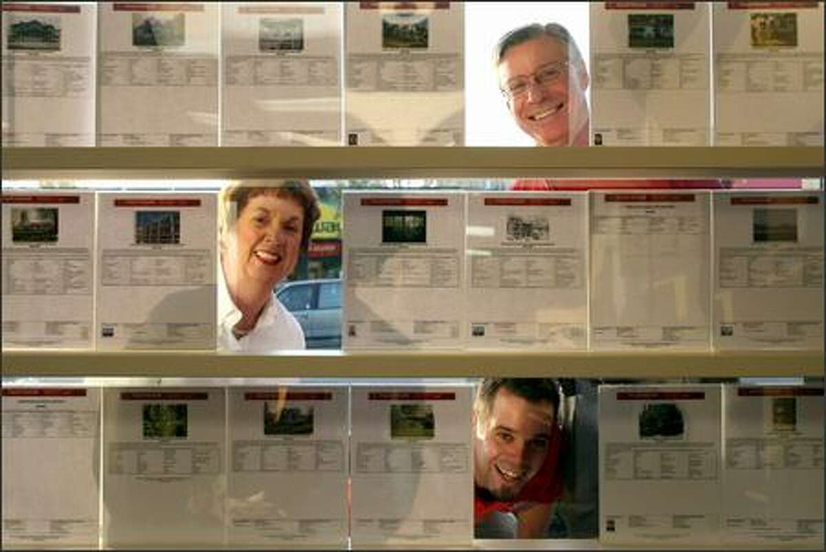 From top, Keller-Williams Realty agents John Thompson, owner/associate broker, his wife Barbara Thompson, lead buyer specialist, and their son David Thompson, lead buyer specialist, look through a few listings in the front window of their West Seattle office.