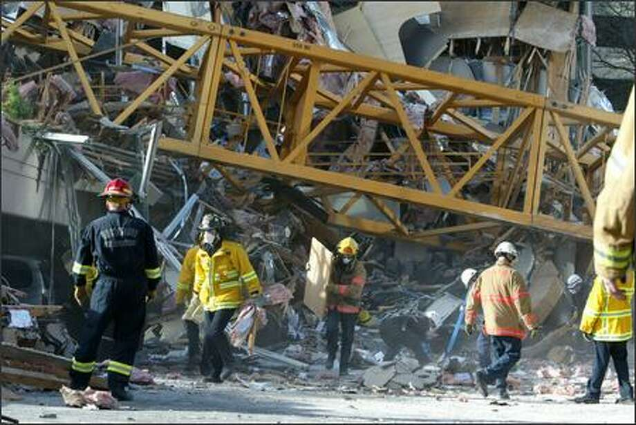 Firefighters and rescue personnel clean up debris as they search for victims in the wreckage of the Plaza 305 building in downtown Bellevue on Friday. A 210-foot construction crane fell on it Thursday night.  One man in a neighboring building was killed. Photo: Gilbert W. Arias, Seattle Post-Intelligencer / Seattle Post-Intelligencer