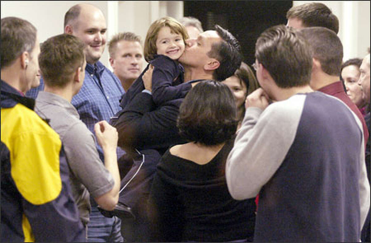 Dino Ross kisses daughter Jillian at campaign headquarters last night after a final count put him narrowly ahead in the governor's race. He stopped short of declaring victory.