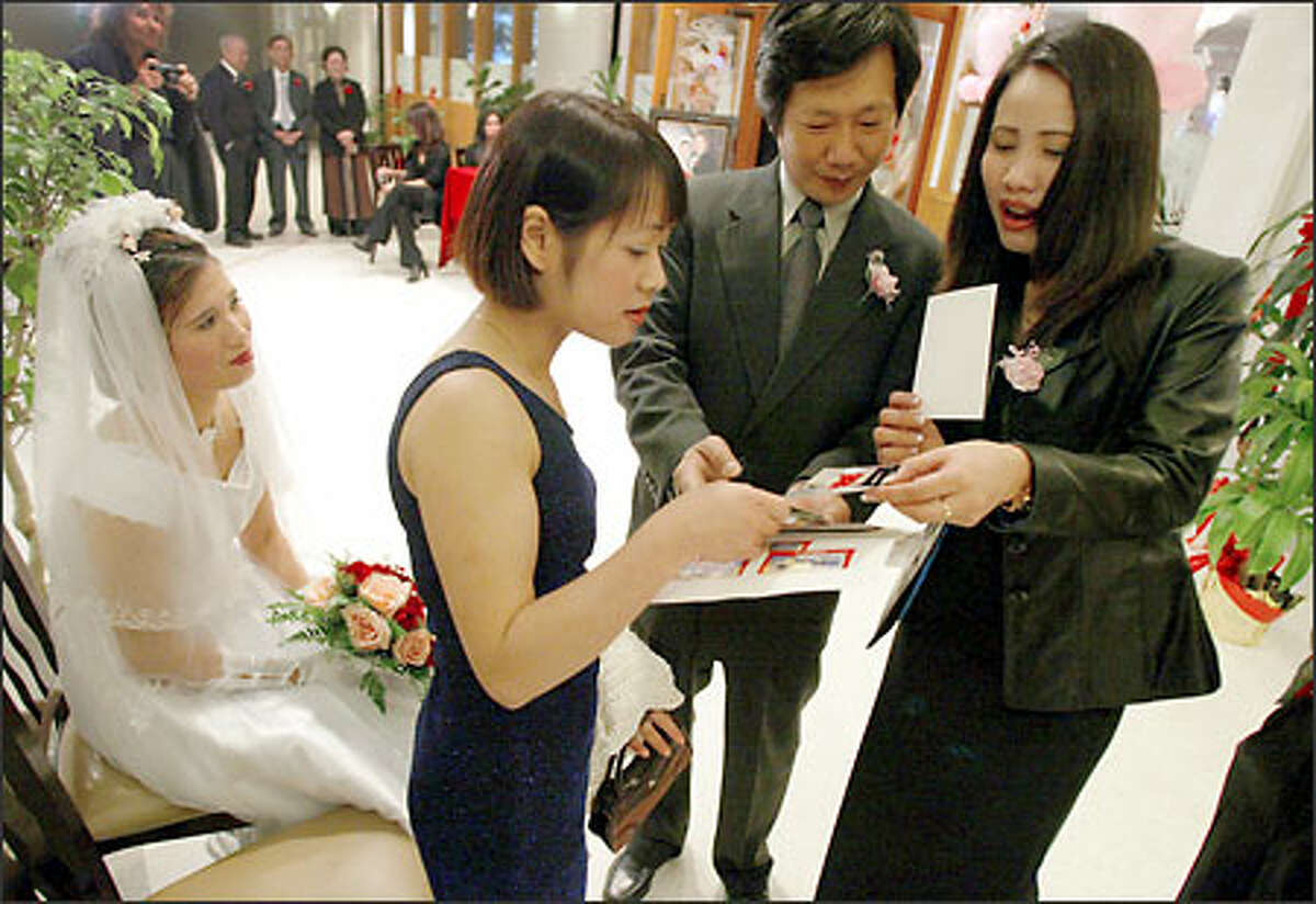 Nga Cao, far left, watches friends she made on American Samoa, Nhung Nong and Giang Hoang, far right, look at photos with Hai-Tri Le, center, as they wait for her wedding banquet to begin.
