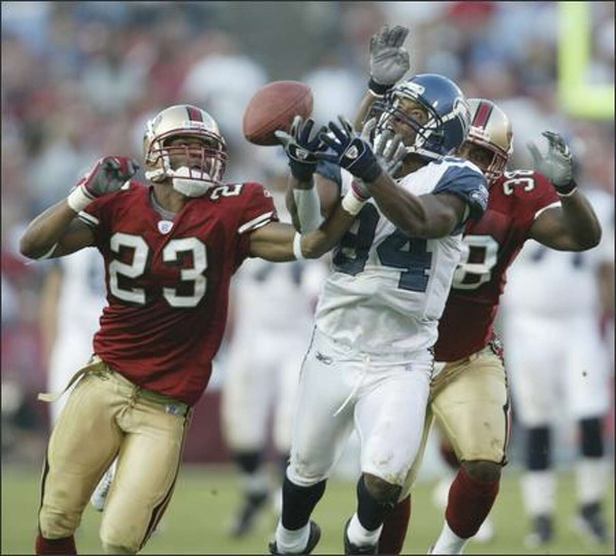Seattle Seahawks receiver Bobby Engram is unable to hang on to a deep pass as San Francisco 49ers Derrick Johnson (23) and Ben Emanuel defend during 4th quarter play.