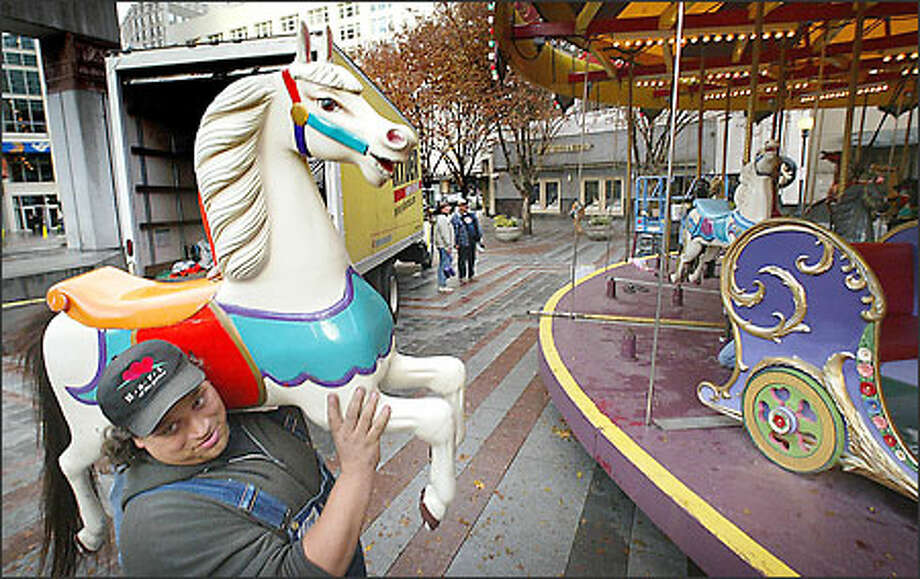 Yousphf Reed, an employee with Wild Waves Enchanted Village Inc., carries one of the 35 horses being installed on the holiday carousel at Westlake Park in downtown Seattle. Each horse has been hand-carved; the lead horse, known as Uncle Sam, is insured for $1 million. The 1906 Parker carousel will open to the public next Friday. It will run through the end of the year. Photo: Dan DeLong, Seattle Post-Intelligencer / Seattle Post-Intelligencer