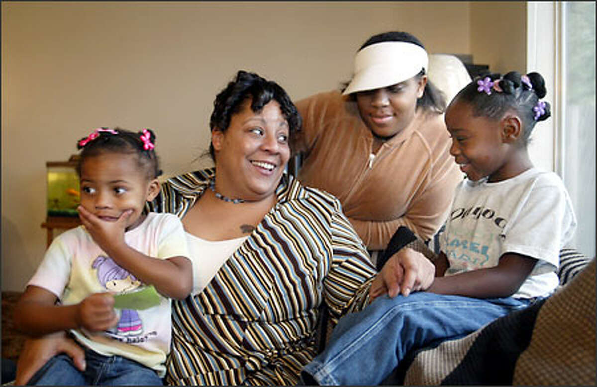 Jesse Miller, second from left, sits with three of her children, from left, Dekari, 3, Janet, 13, and Deasia, 6, in their Tacoma home. They are past recipients of the Forgotten Children's Fund.