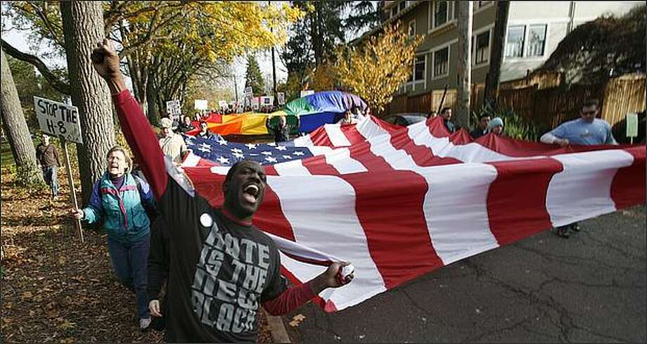 Chris Porter carried a corner of a huge American flag from Volunteer Park to Westlake Center in the march for marriage equality on Saturday, November 15, 2008. Photo: Paul Joseph Brown, Seattle Post-Intelligencer / Seattle Post-Intelligencer