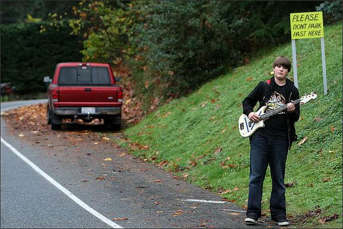 Wolfgang Olson, 13, plays his bass guitar as he waits for the school bus in Lake Forest Park. Olson is a seventh grader at Room Nine Community School.