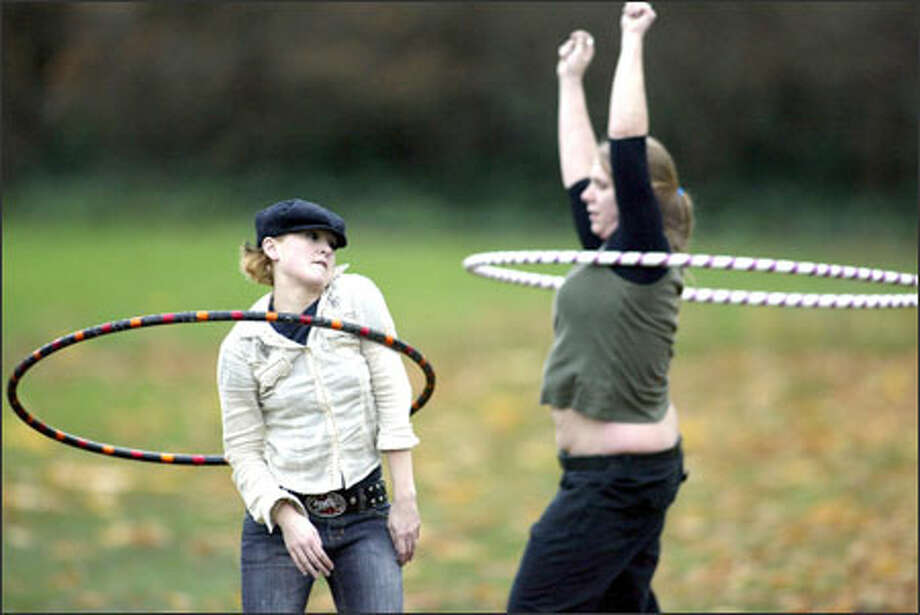 K.C. Vandemerkt of Chicago, left, and Donia Love of Seattle try to keep the hula hoops moving as they have a little fun and get in some exercise during an outing at Seattle's Volunteer Park recently. The hula hoop is an ancient invention; the original ones were made from metal, bamboo, wood, grasses and vines. Photo: Jim Bryant, Seattle Post-Intelligencer / Seattle Post-Intelligencer