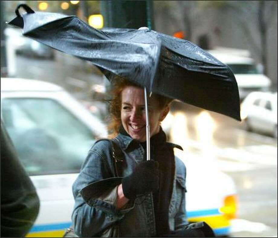 """""""This is unusual, isn't it?"""" said Lara Gordon, visiting from Puerto Rico, about the rainy, windy weather in downtown Seattle Tuesday.  Not really: November 2006 is the wettest month ever in the Seattle area, thanks to a series of storms. Photo: Karen Ducey, Seattle Post-Intelligencer / Seattle Post-Intelligencer"""