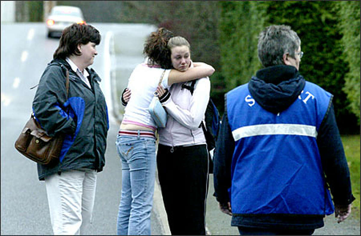Neighbors console one another near the scene of an apparent murder-suicide in Edmonds on Monday. Police found the bodies of a father and his two daughters.